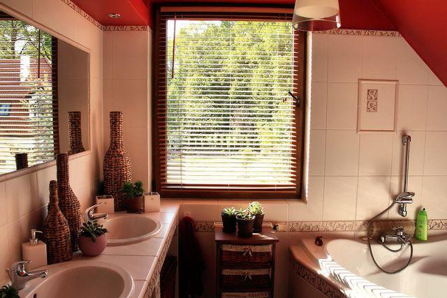 Aranżacja łazienki na poddaszu w beżu i czerwieni