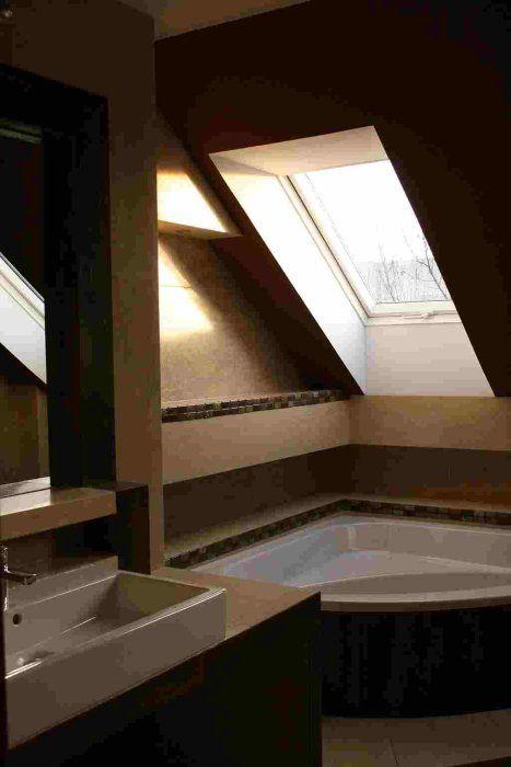 Wanna narożna pod ukośnym sufitem z oknem dachowym