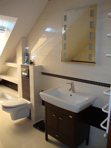 Drewniana szafka pod umywalkę w łazience na poddaszu