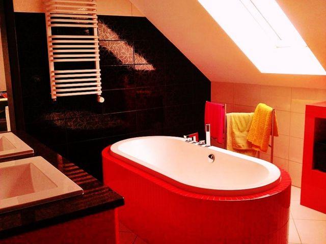 Wanna wolnostojąca zabudowana czerwonymi płytkami w łazience na poddaszu