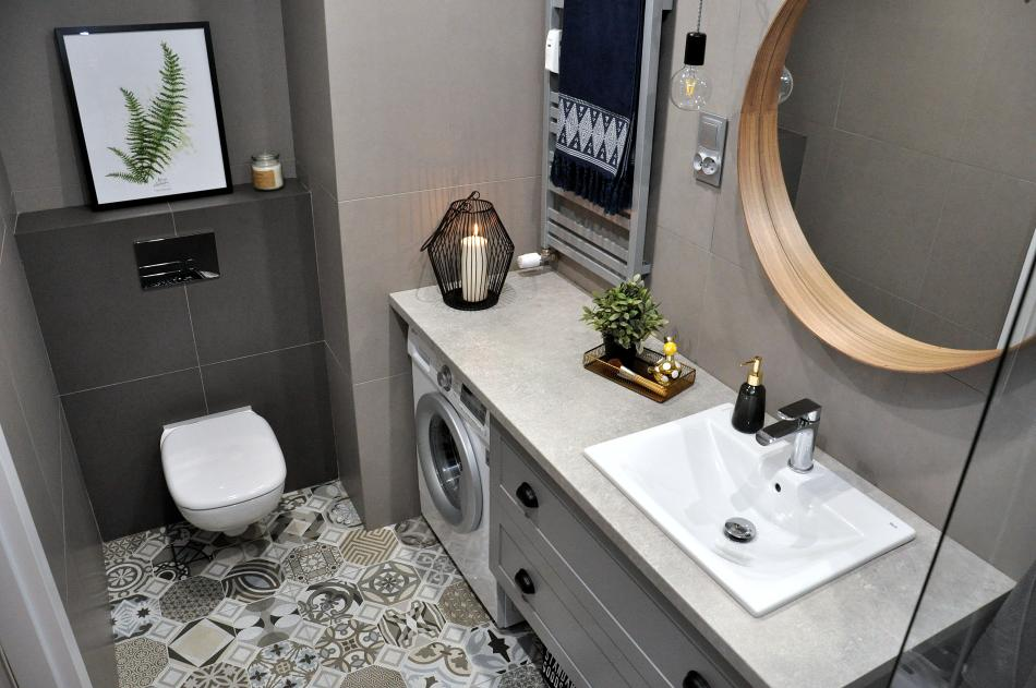 Aranżacja małej łazienki w odcieniach szarości z dekoracyjnym motywem liścia palmy