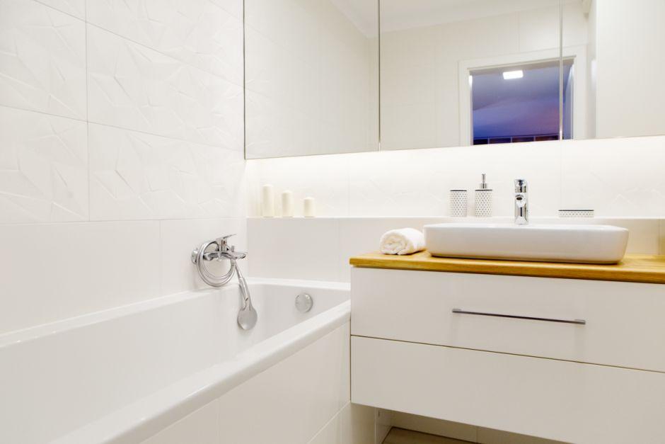 Wanna w białej łazience z chromowaną armaturą