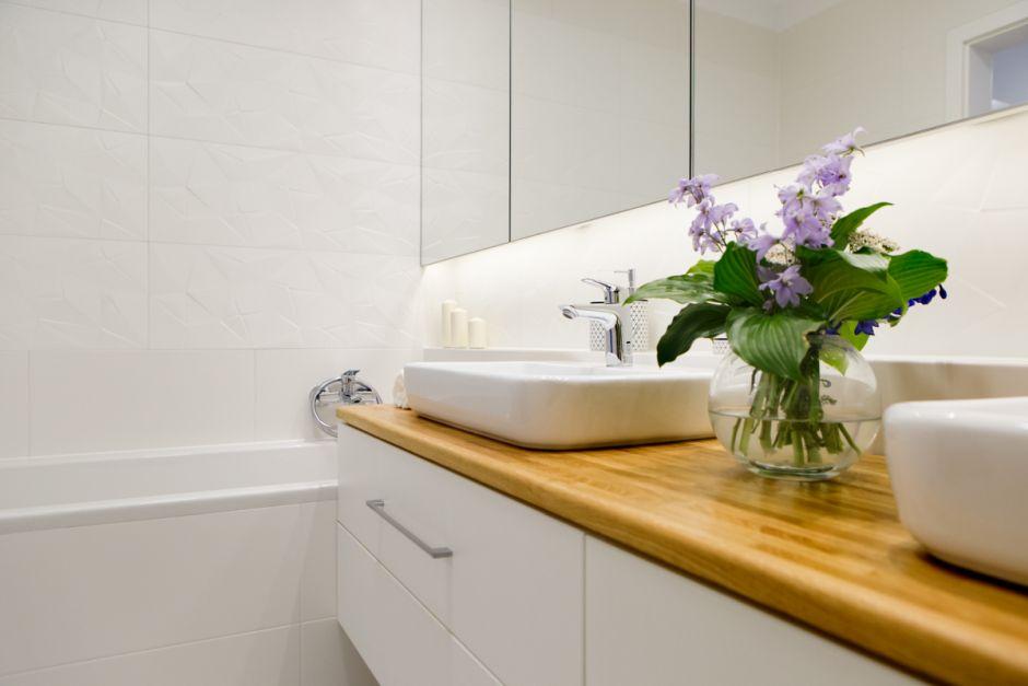 Płytki strukturalne nad wanną w białej łazience