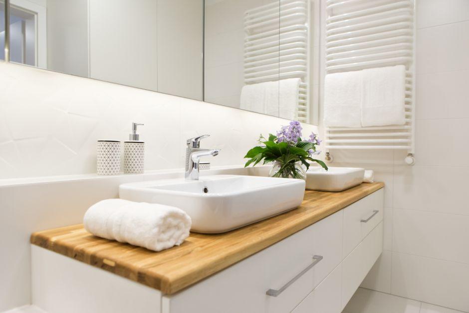 Biała łazienka z drewnianym blatem pod umywalkę
