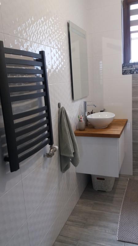 Białe, błyszczące płytki strukturalne na ścianie w łazience