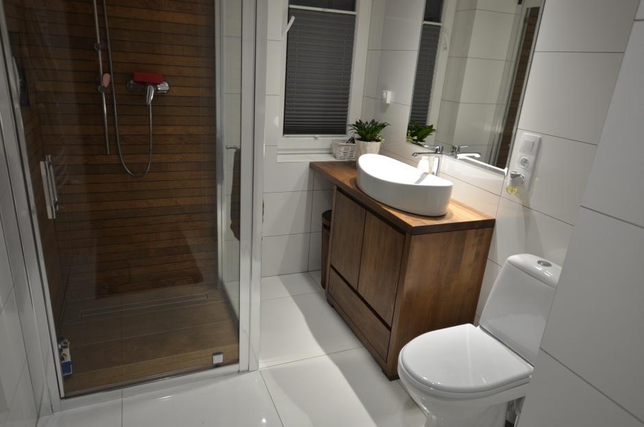 Szafka łazienkowa z drewna dębowego wybarwiona na kolor dopasowany do płytek drewnopodobnych w kabinie prysznicowej