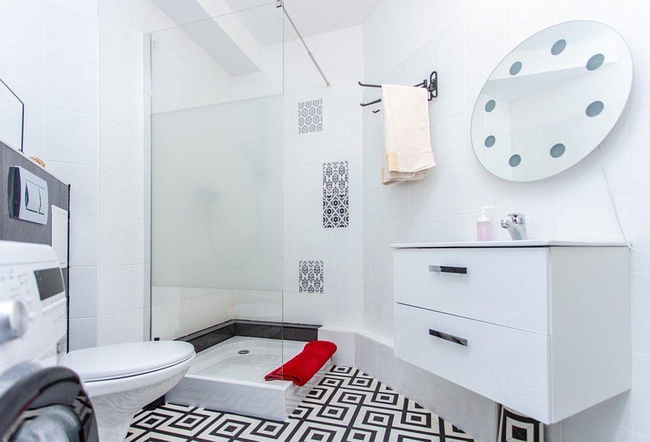 Biało-czarna łazienka z okrągłym lustrem