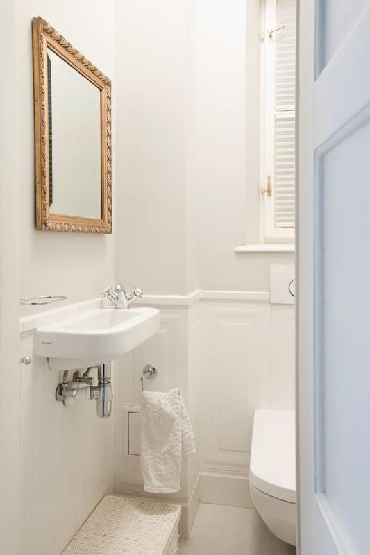 Złota rama lustra w małej białej łazience