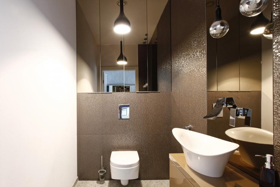 Zabudowa stelaża WC z szafką o lustrzanych frontach w brązowej łazience