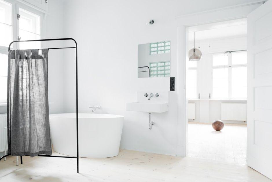 Wanna wolnostojąca w minimalistycznej białej łazience z lustrem