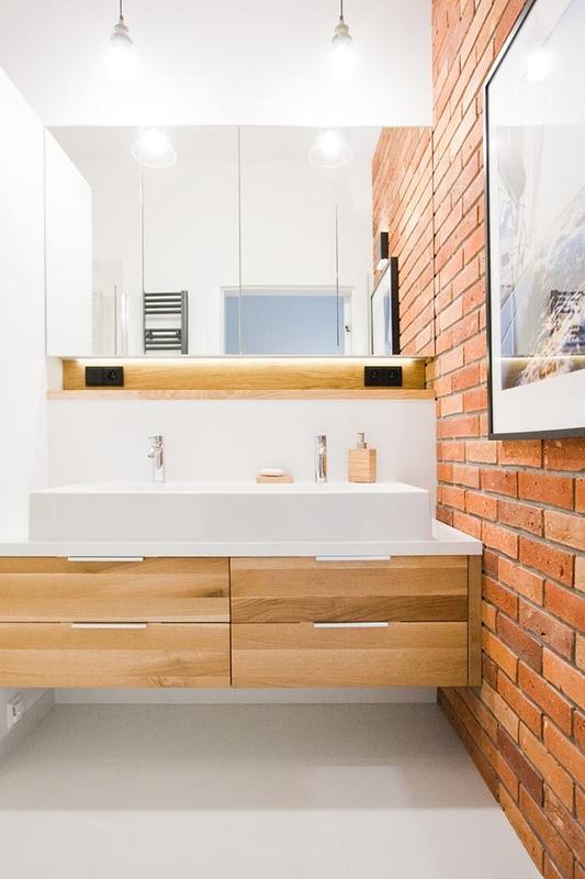 Szafka z lustrzanymi frontami w łazience z cegłą na ścianie