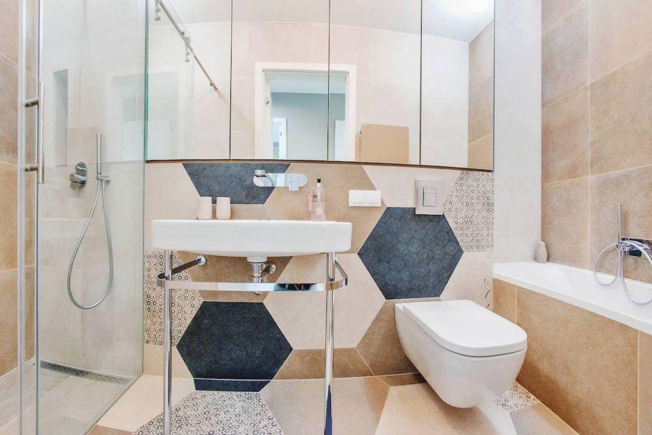 Szafka z lustrem w łazience z heksagonami na ścianie