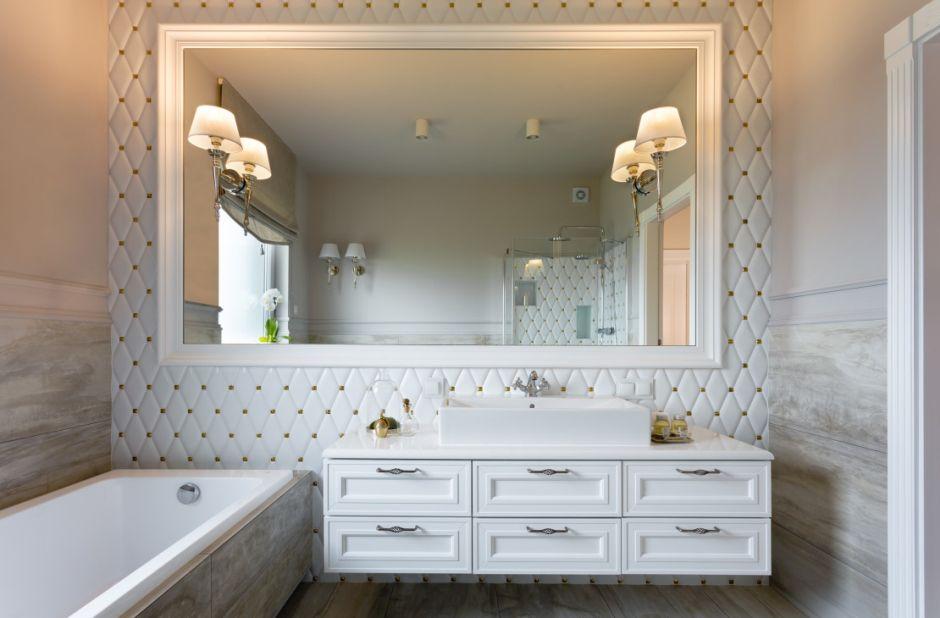 Pikowane płytki i duże lustro w białej ramie w aranżacji łazienki