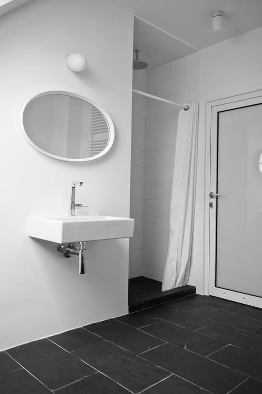Owalne lustro w minimalistycznej łazience na poddaszu