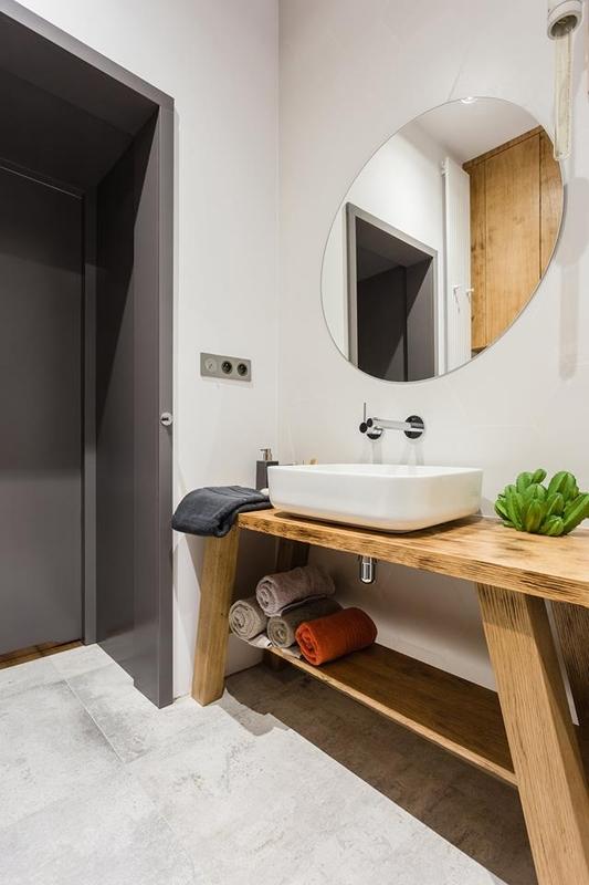 Okrągłe lustro w łazience z drewnianą szafką pod umywalkę
