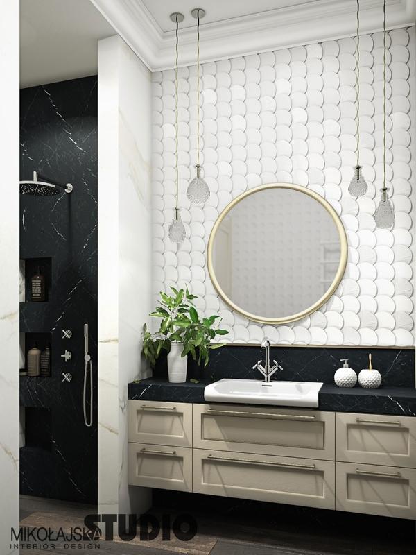 Okrągłe lustro ze złota ramą w łazience z płytkami strukturalnymi na podłodze