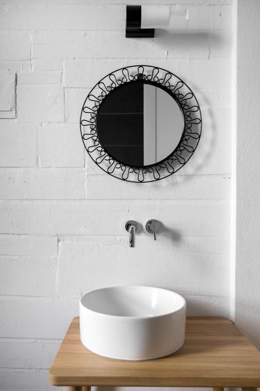 Okrągłe lustro z czarną metalową ramą w łazience loft