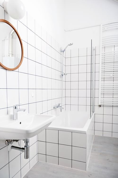 Okrągłe lustro z drewnianą ramą w łazience z płytkami subway