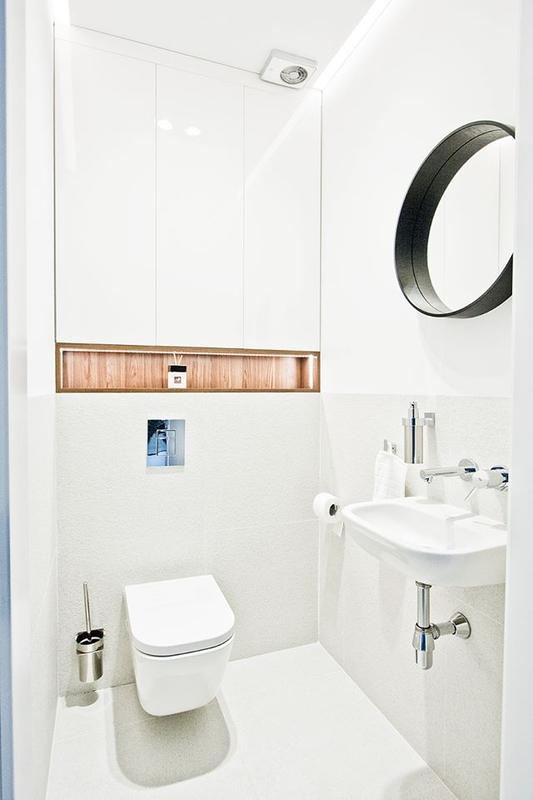 Okrągłe lustro z czarną ramą w małej łazience