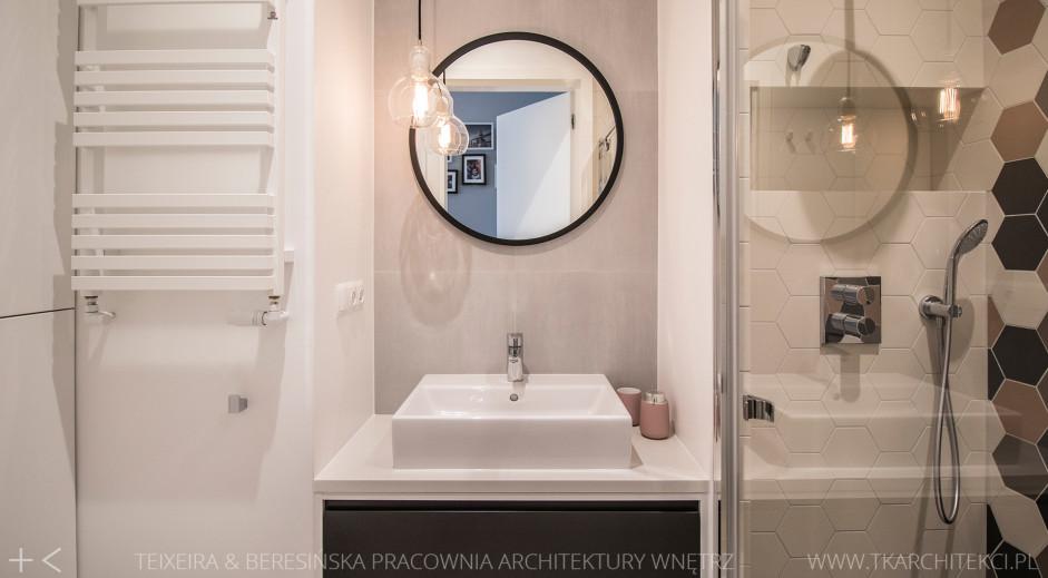 Okrągłe lustro z czarną ramą w łazience z heksagonami