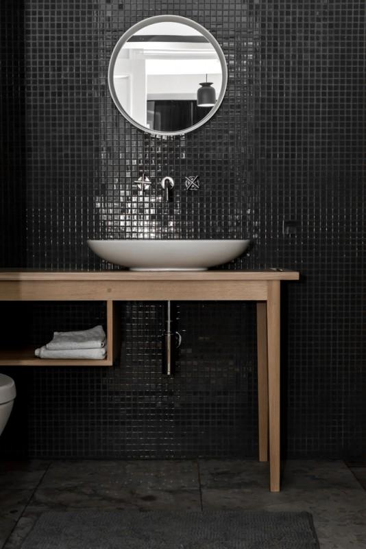 Okrągłe lustro w łazience z czarną mozaiką na ścianie