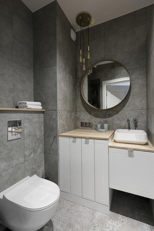 Okrągłe lustro w szarej łazience