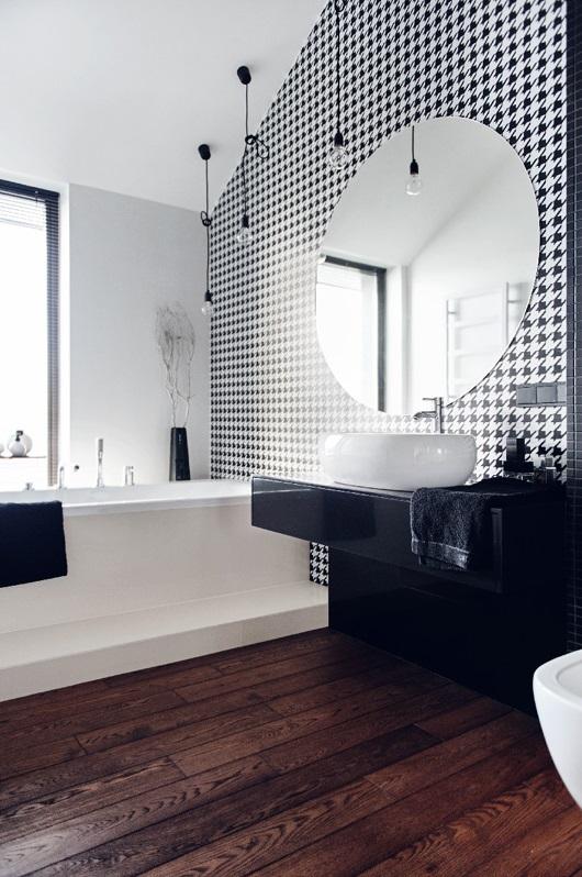Okrągłe lustro w łazience z biało-czarną pepitką na ścianie