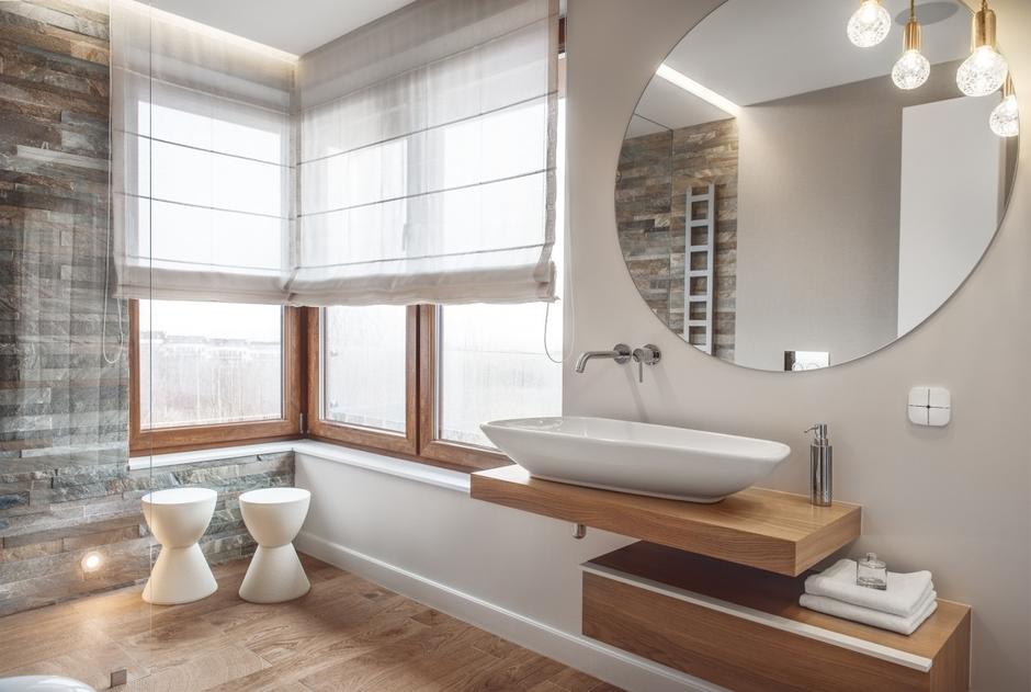 Okrągłe lustro w łazience z białą umywalką nablatową