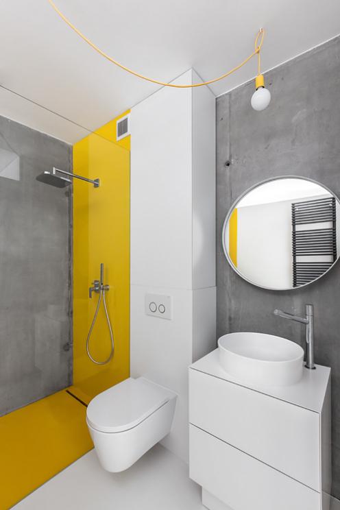 Okragłe lustro w łazience z betonem na ścianie