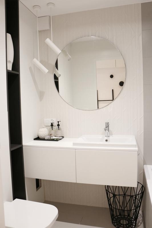 Okrągłe lustro w biało-czarnej łazience