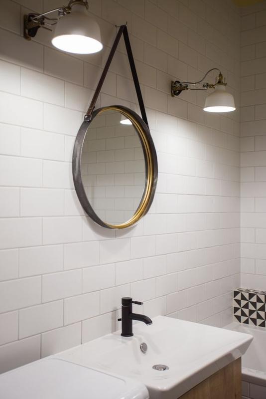 Okrągłe lustro na pasku oraz lampy industrialne w aranżacji łazienki