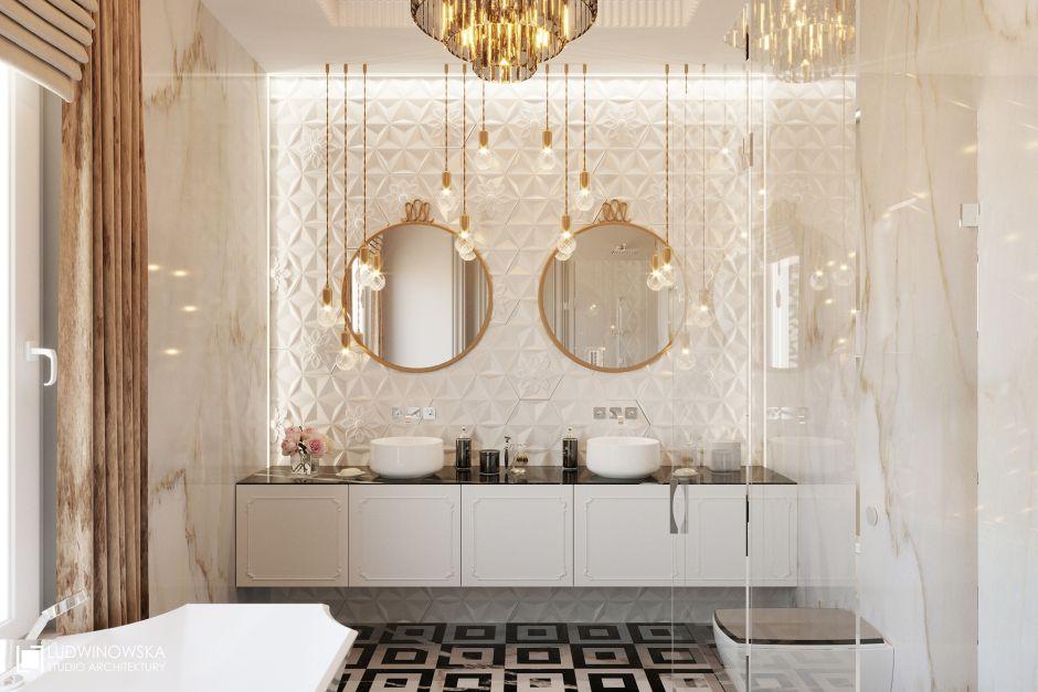 Okrągłe lustro ze złotymi ramami w łazience z płytkami strukturalnymi na ścianie