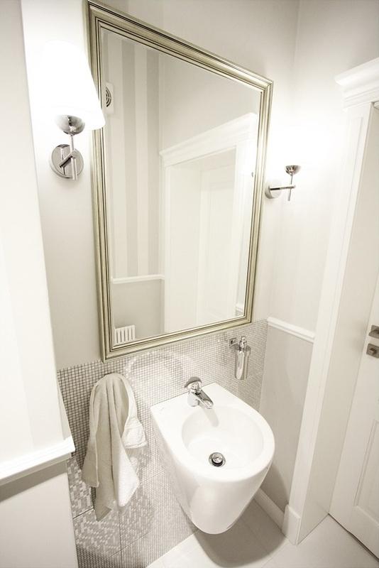 Metaliczna rama lustra w jasnej łazience