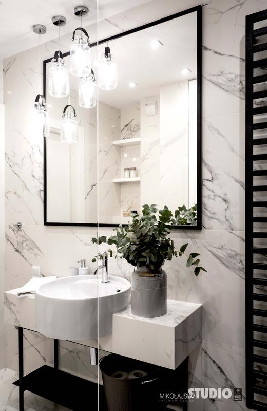Marmurowa łazienka z dużym lustrem w czarnej łazience
