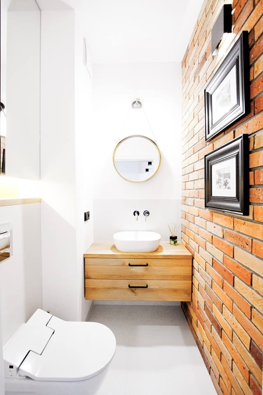 Małe okrągłe lustro w łazience z cegłą na ścianie