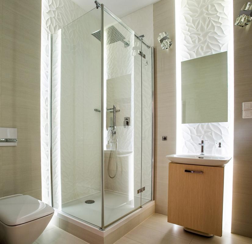 Małe lustro z podświetleniem w łazience z kabina prysznicową