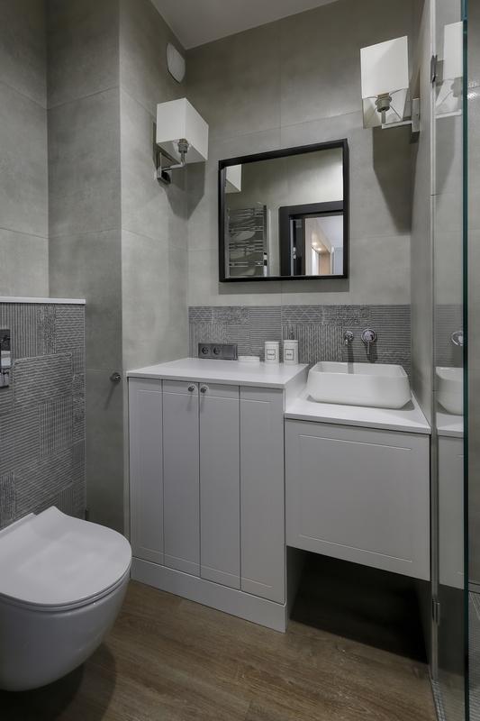 Małe kwadratowe lustro w szarej łazience