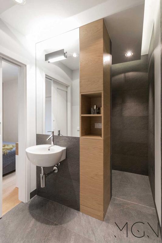 Mała wąska łazienka z lustrem i wiszącą umywalką