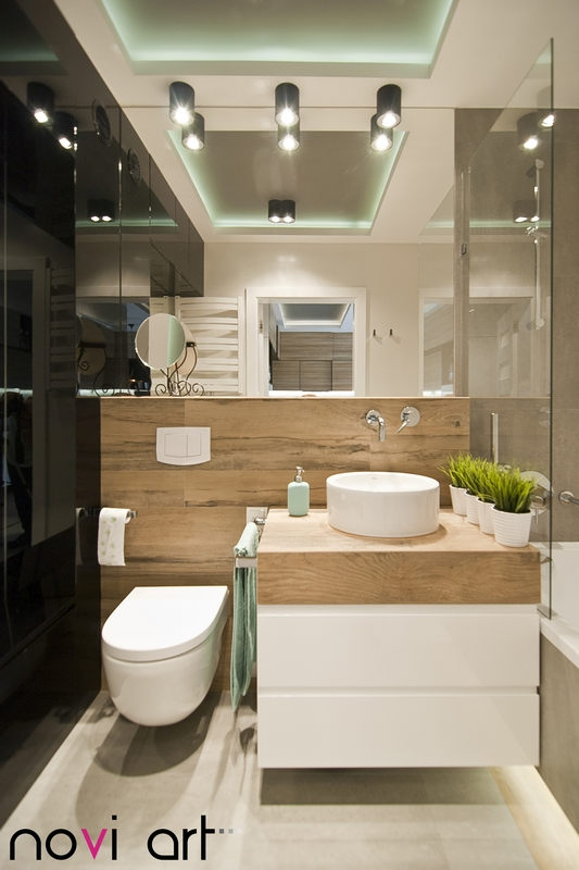 Mała umywalka nablatowa w łazience z dużym lustrem