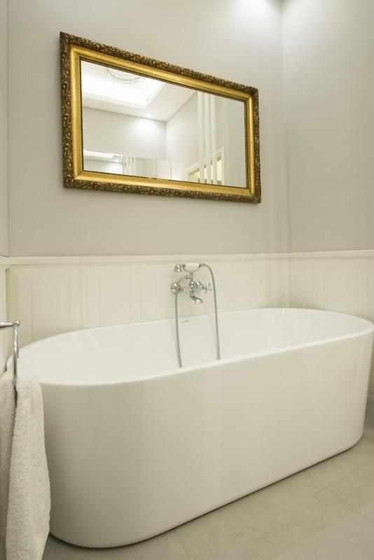 Lustro ze złotą ramą nad wanną wolnostojącą w łazience