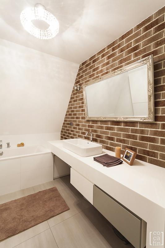 Lustro w miedzianej ramie w łazience z czerwoną cegłą na ścianie