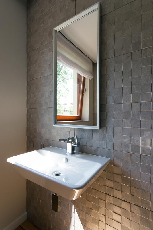 Lustro w szarej łazience z płytkami strukturalnymi na ścianie
