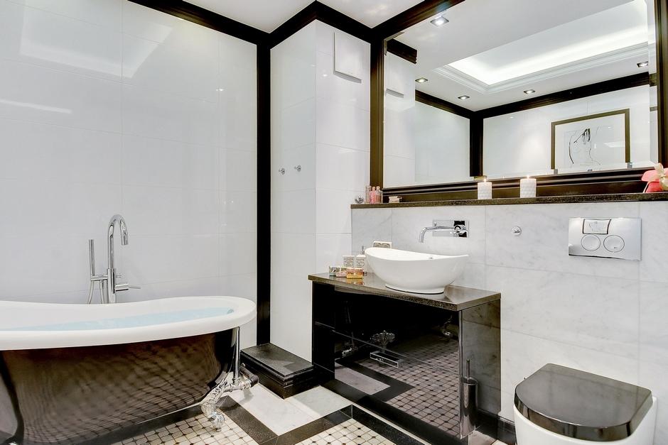 Lustro w eleganckiej łazience z wanną na lwich łapach
