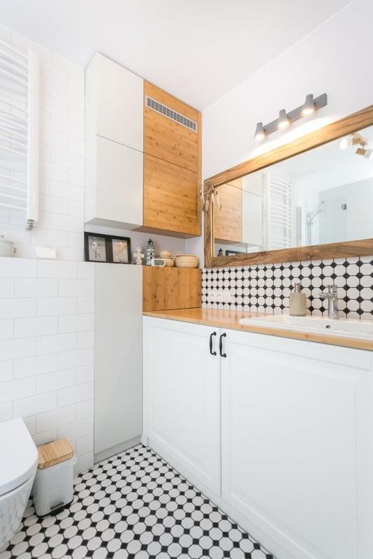 Lustro w drewnianej ramie w łazience z biało-czarną płytką na podłodze