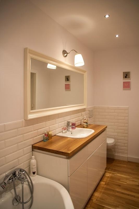 Lustro w białej drewnianej ramie w jasnej łazience