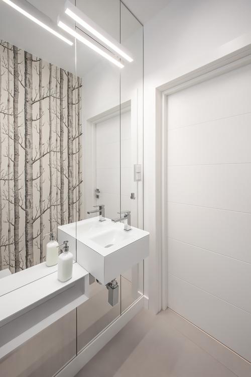 Lustro pokrywające ścianę w łazience z tapetą