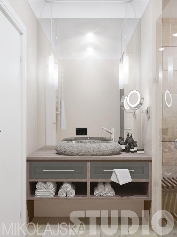 Lustro pokrywające całą ścainę w łazience z kamienną umywalką