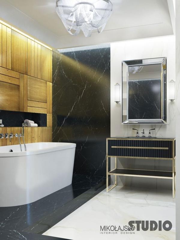 Lustro o lustrzanej ramie w łazience ze złotymi płytkami na ścianie
