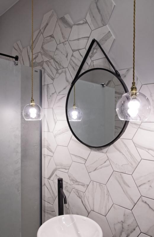 Lustro na czarnym pasku w łazience z marmurowymi heksagonami