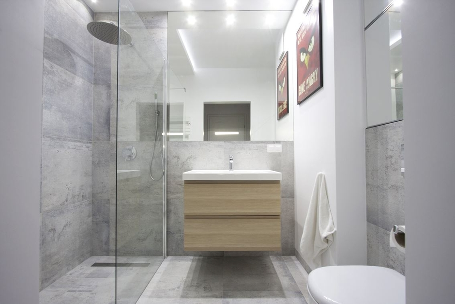 Kwadratowe lustro nad umywalką w łazience z prysznicem